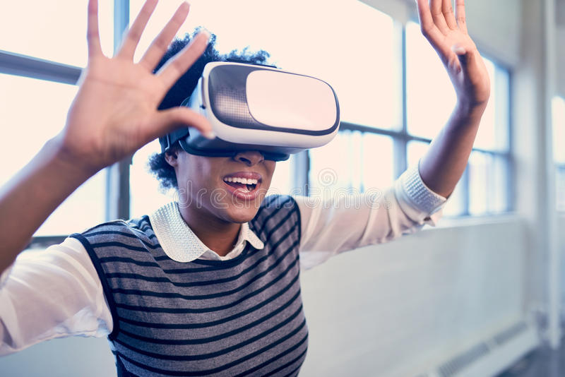 Mujer negra milenaria fresca que explora los vidrios de la realidad virtual en un espacio del abierto-concepto foto de archivo