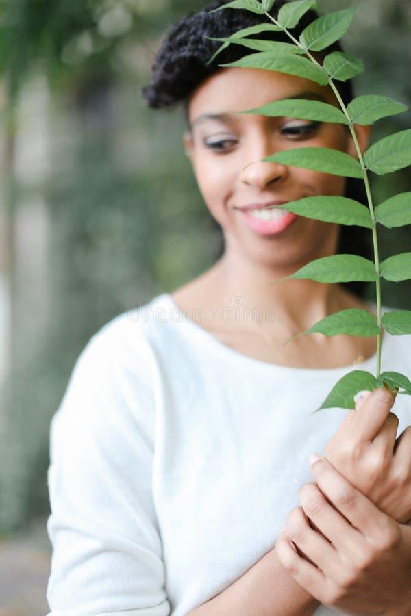 Mujer negra nigeriana a medias americana con las explosiones que se colocan con la hoja verde, blusa blanca que lleva fotos de archivo libres de regalías