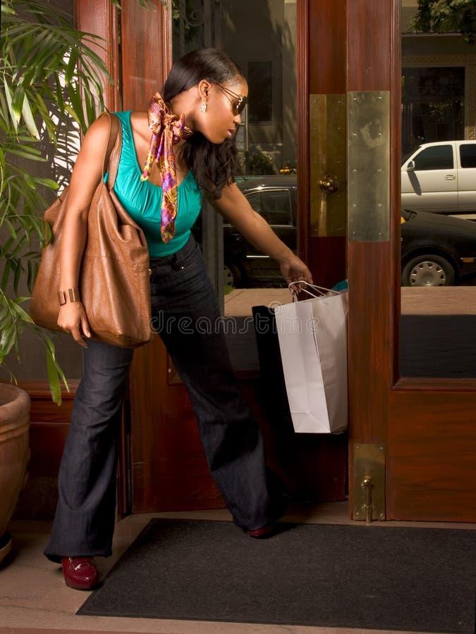 Mujer negra pegada en la puerta (foco en bolso) imágenes de archivo libres de regalías