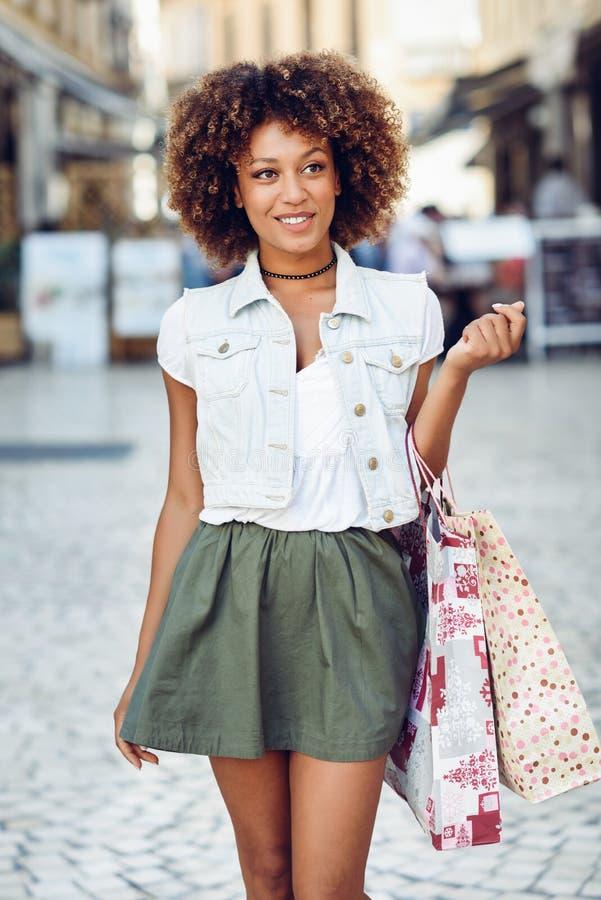 Mujer negra, peinado afro, con los panieres en la calle foto de archivo