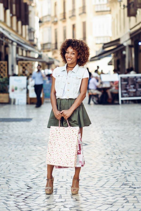 Mujer negra, peinado afro, con los panieres en la calle imagen de archivo libre de regalías