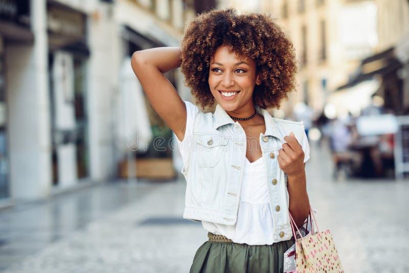 Mujer negra, peinado afro, con los panieres en la calle fotos de archivo