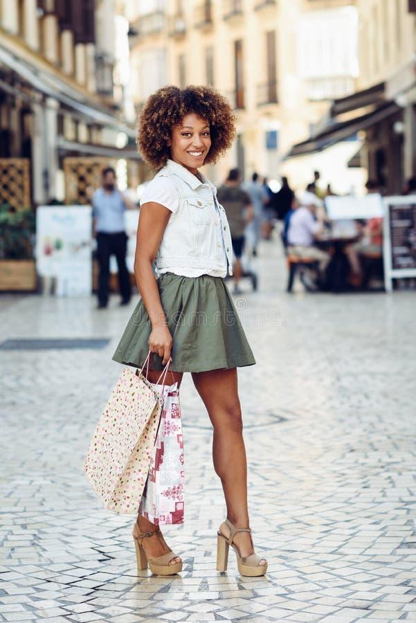 Mujer negra, peinado afro, con los panieres en la calle fotografía de archivo