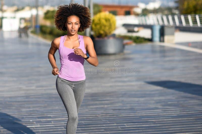 Mujer negra, peinado afro, corriendo al aire libre en camino urbano foto de archivo libre de regalías