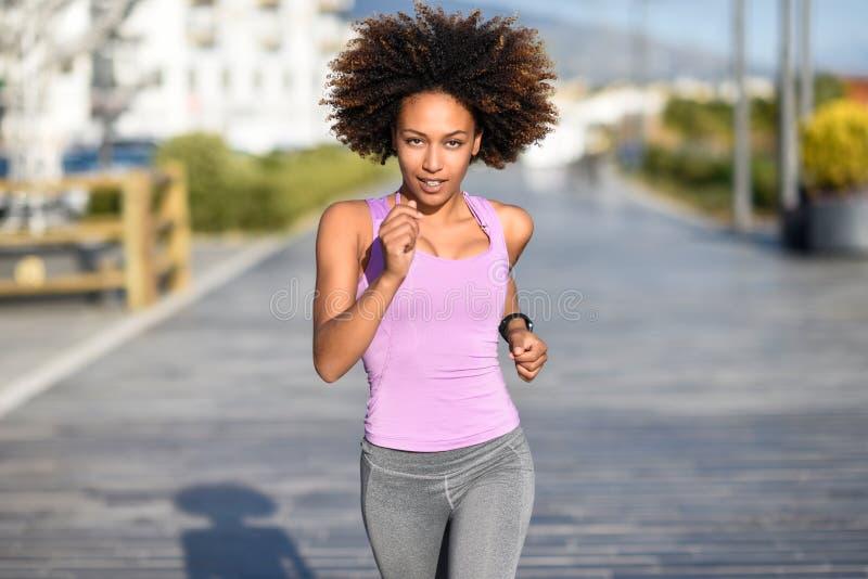Mujer negra, peinado afro, corriendo al aire libre en camino urbano imagen de archivo libre de regalías