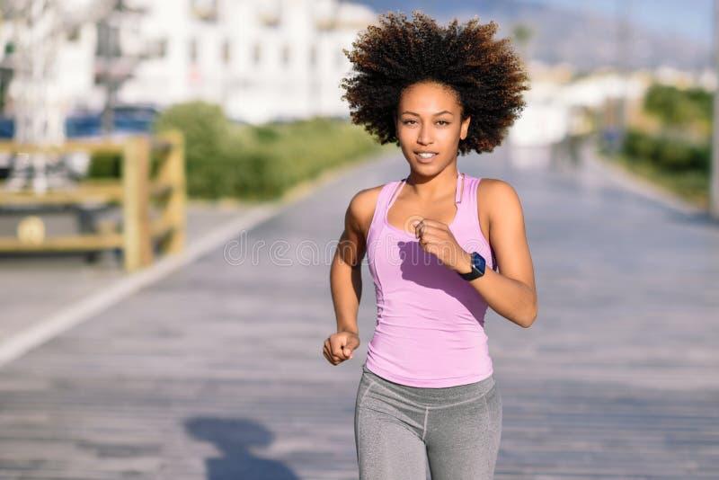 Mujer negra, peinado afro, corriendo al aire libre en camino urbano fotografía de archivo libre de regalías