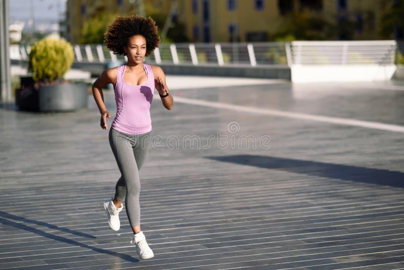 Mujer negra, peinado afro, corriendo al aire libre en camino urbano foto de archivo