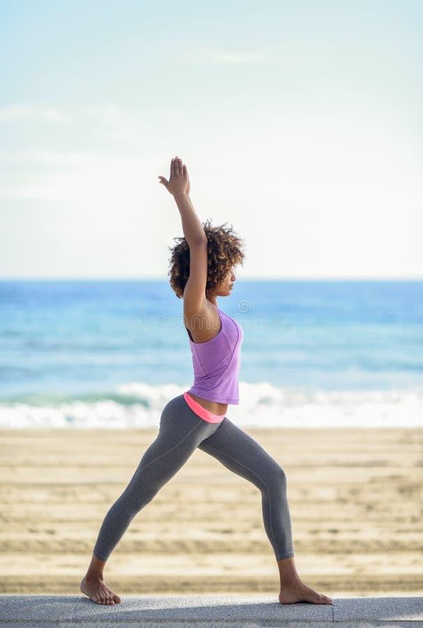 Mujer negra, peinado afro, haciendo yoga en actitud del guerrero en el b fotos de archivo libres de regalías