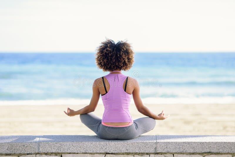Mujer negra, peinado afro, haciendo yoga en la playa fotografía de archivo