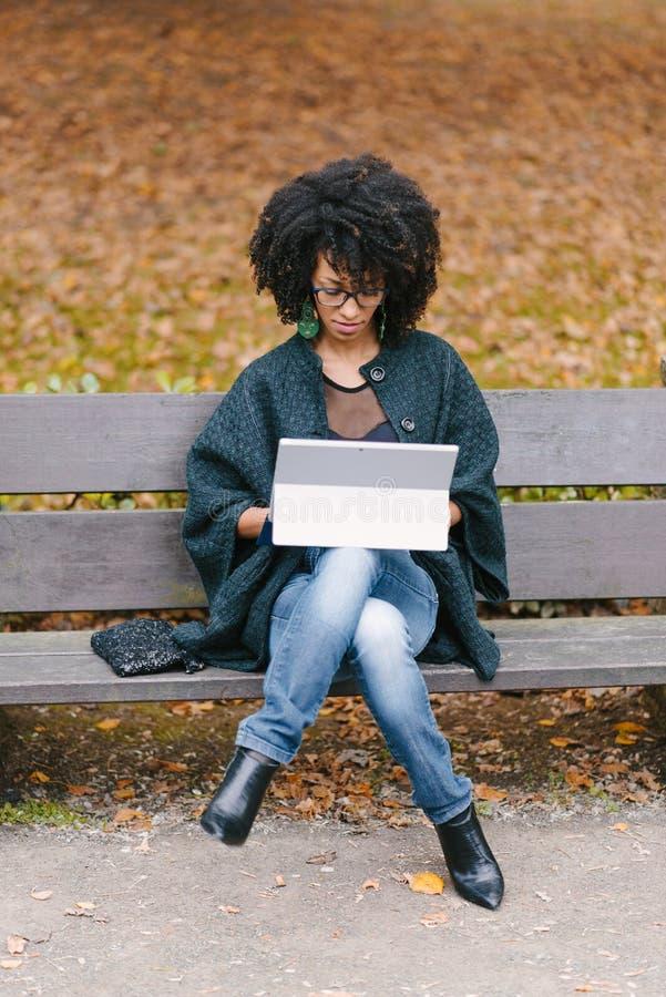 Mujer negra profesional que trabaja con el ordenador portátil afuera en otoño foto de archivo