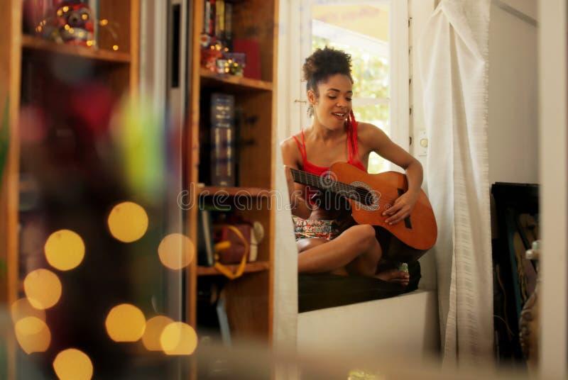Mujer negra que canta y que toca la guitarra en casa imagenes de archivo