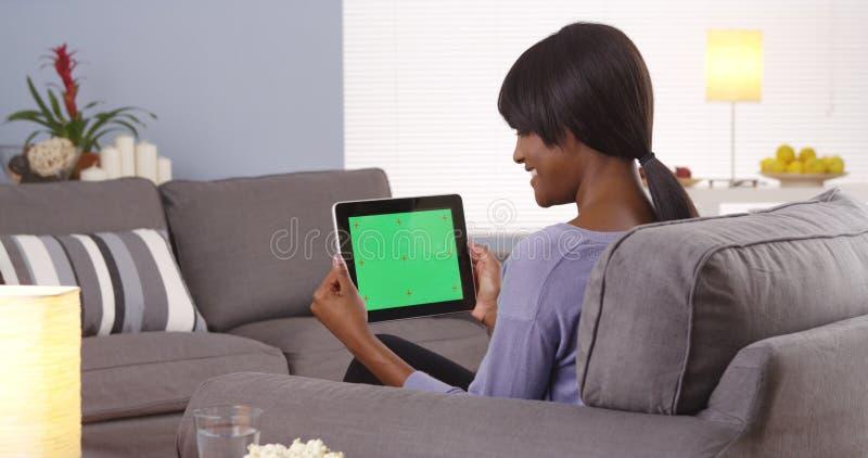 Mujer negra que habla con la tableta foto de archivo