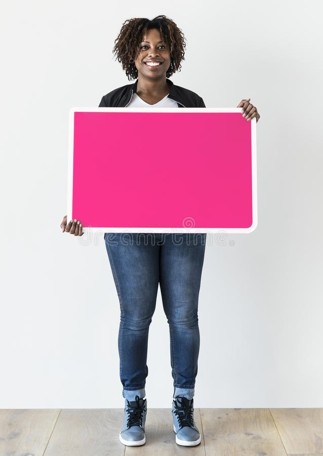 Mujer negra que lleva a cabo al tablero en blanco fotografía de archivo libre de regalías