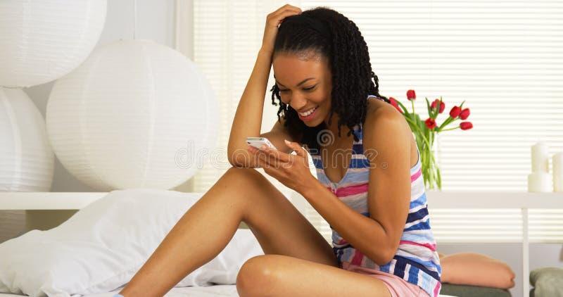 Mujer negra que manda un SMS y que ríe imagen de archivo libre de regalías