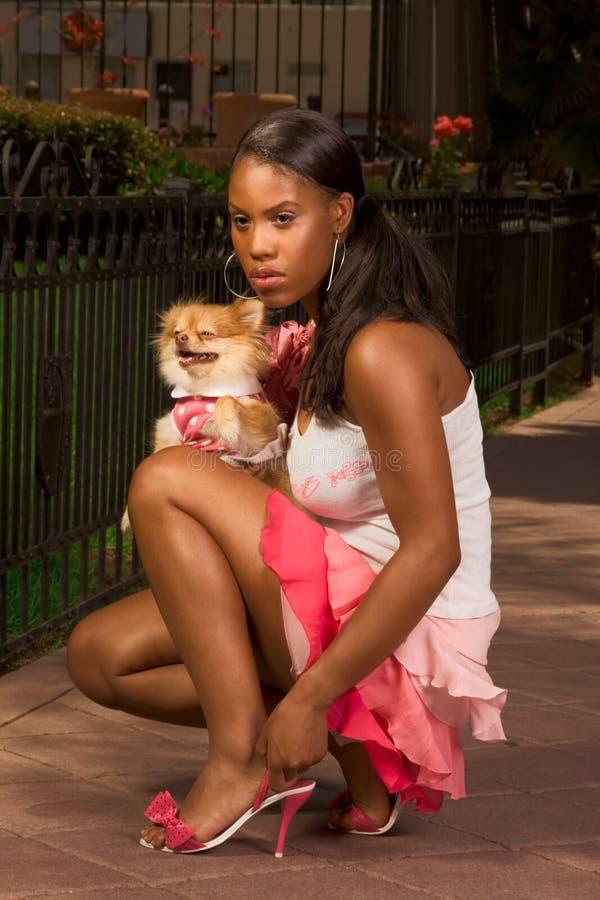 Mujer negra que se pone en cuclillas, con el perro del perro de Pomerania de Pomeranian imagen de archivo libre de regalías