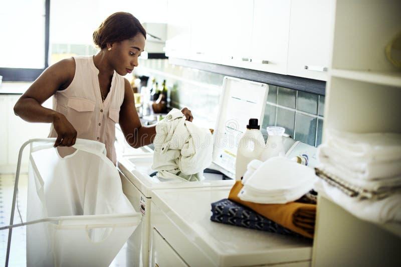 Mujer negra que usa la lavadora que hace el lavadero fotos de archivo
