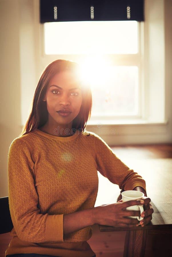 Mujer negra seria en la tabla delante de la ventana imagen de archivo libre de regalías