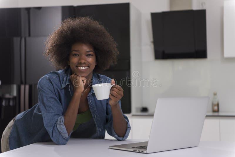 Mujer negra sonriente en cocina moderna imagen de archivo libre de regalías