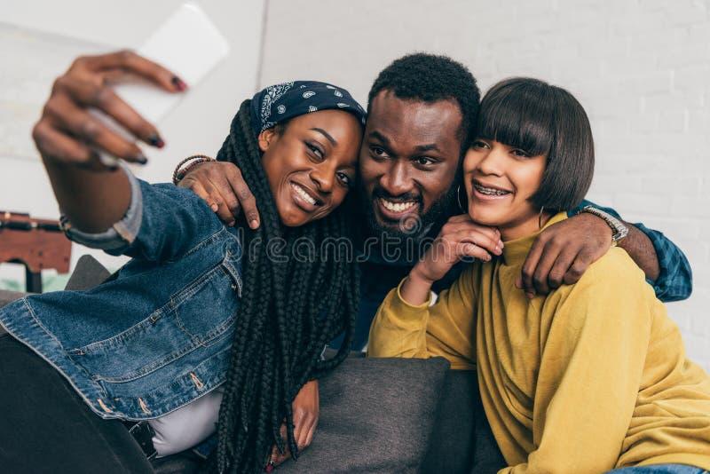 mujer negra sonriente que toma el selfie con dos imagenes de archivo