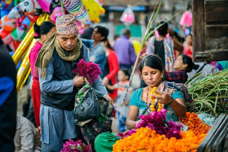 Mujer nepalesa que vende las flores en un mercado local en Nepal foto de archivo