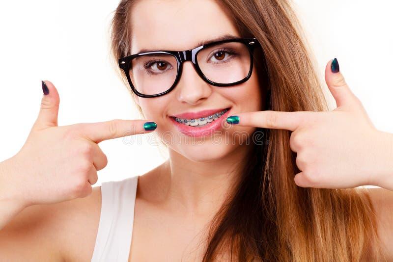 Mujer Nerdy que muestra sus dientes con los apoyos imagen de archivo