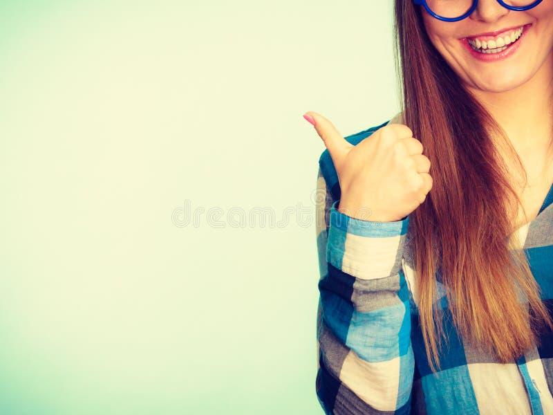 Mujer nerdy sonriente feliz que muestra el pulgar para arriba imágenes de archivo libres de regalías