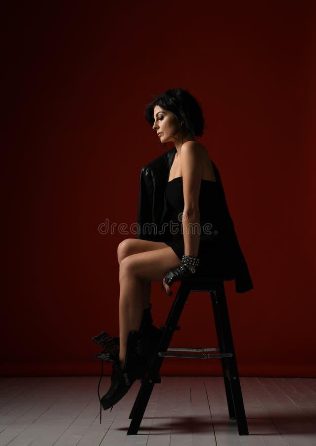 Mujer nerviosísima tensa en el vestido apretado negro, la chaqueta de cuero y las botas brutales grandes sentándose en una escale imagen de archivo