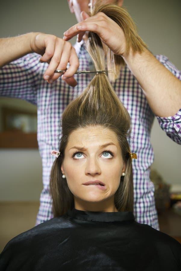 Mujer nerviosa en la tienda del peluquero que corta el pelo largo imagenes de archivo