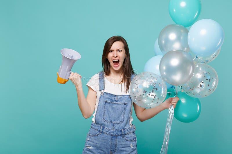 Mujer nerviosa en ropa del dril de algodón que jura, megáfono del control del grito mientras que celebra con los balones de aire  foto de archivo