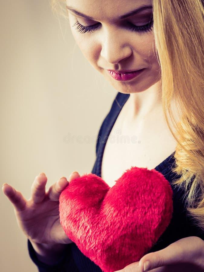 Mujer nostálgica que lleva a cabo el corazón rojo imágenes de archivo libres de regalías
