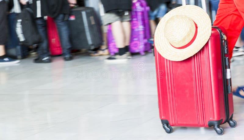 Mujer nuestro sombrero del bolso y de paja del equipaje de la maleta del hombre que camina en el aeropuerto fotografía de archivo libre de regalías