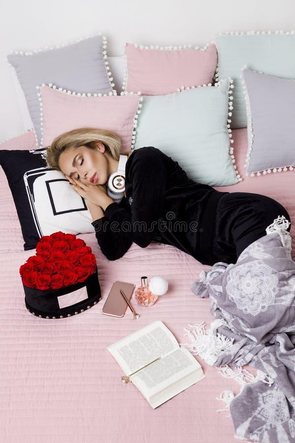 Mujer o adolescente feliz con los auriculares que escucha la música del smartphone Muchacha hermosa en el pijama que miente en ca imagen de archivo