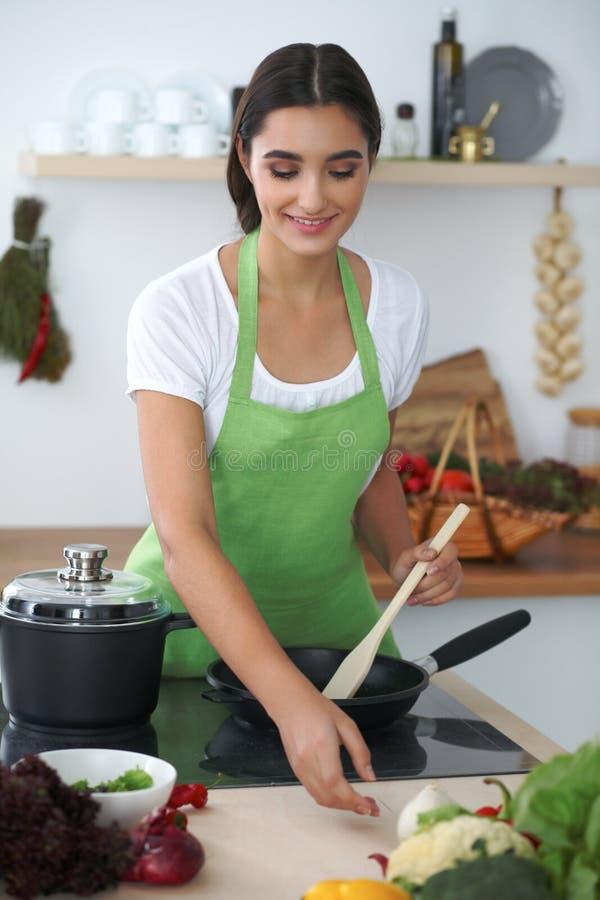 Mujer o estudiante hispánica joven que cocina en cocina foto de archivo