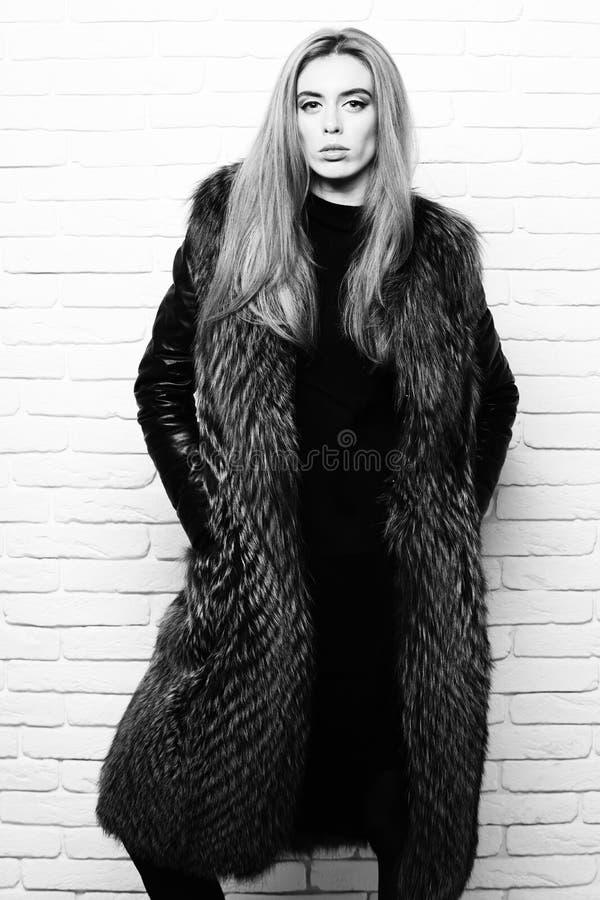 Mujer o muchacha bonita de moda joven con el pelo rubio largo hermoso en la capa de la cintura de la piel de Borgoña con negro imagenes de archivo