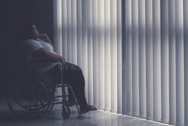 Mujer obesa pensativa que se sienta en la silla de ruedas imagenes de archivo