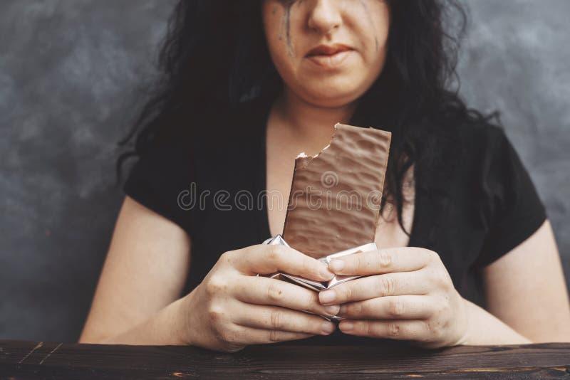 mujer obesa que come el chocolate codicioso y el griterío foto de archivo