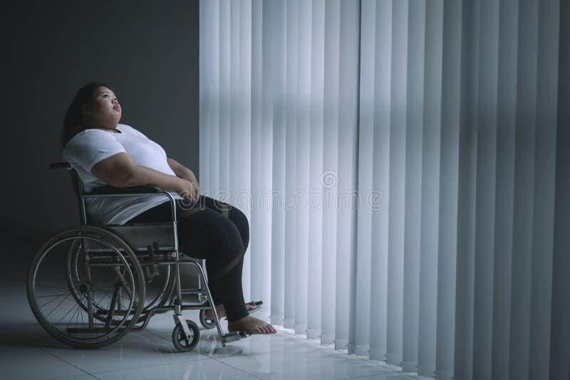 Mujer obesa sola que se sienta en la silla de ruedas imagen de archivo libre de regalías