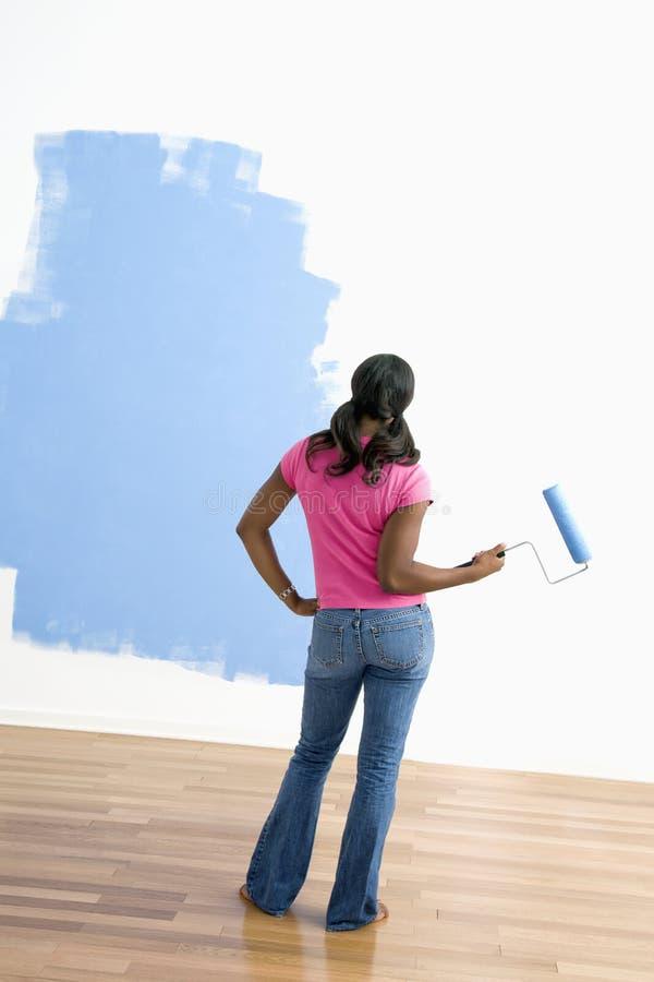Mujer observando trabajo de la pintura. fotos de archivo