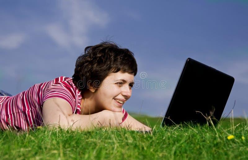 Mujer ocasional joven que trabaja en la computadora portátil imagen de archivo libre de regalías
