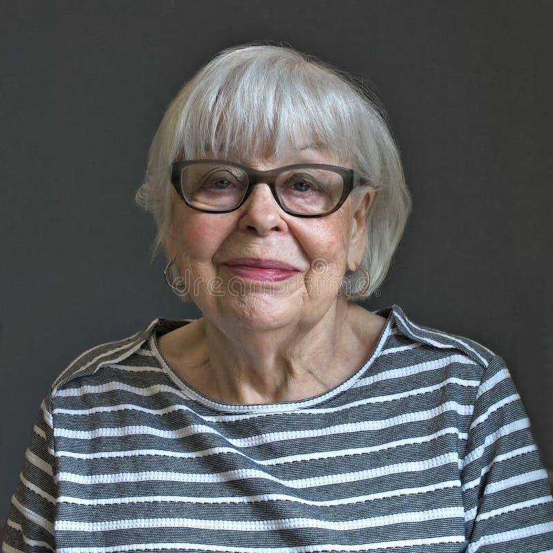 Mujer octogenaria mayor en top rayado con el fondo gris imagenes de archivo