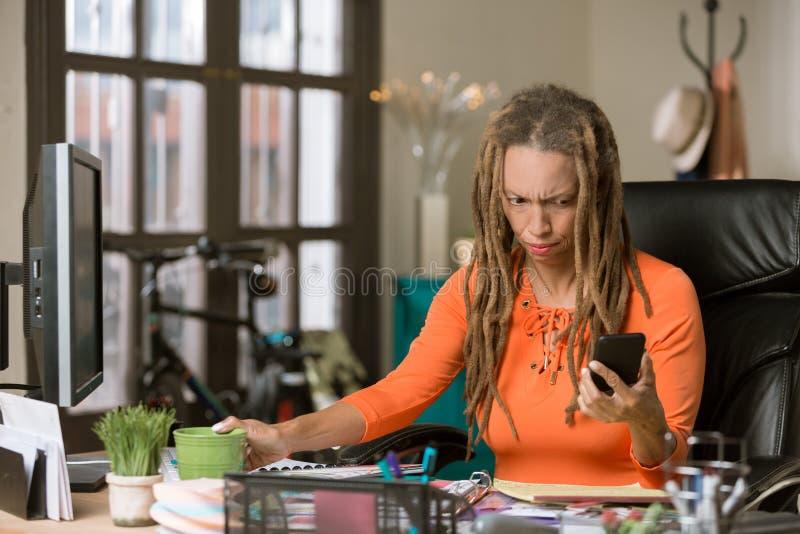 Mujer ocupada con Drealocks que reacciona a su tel?fono imagen de archivo