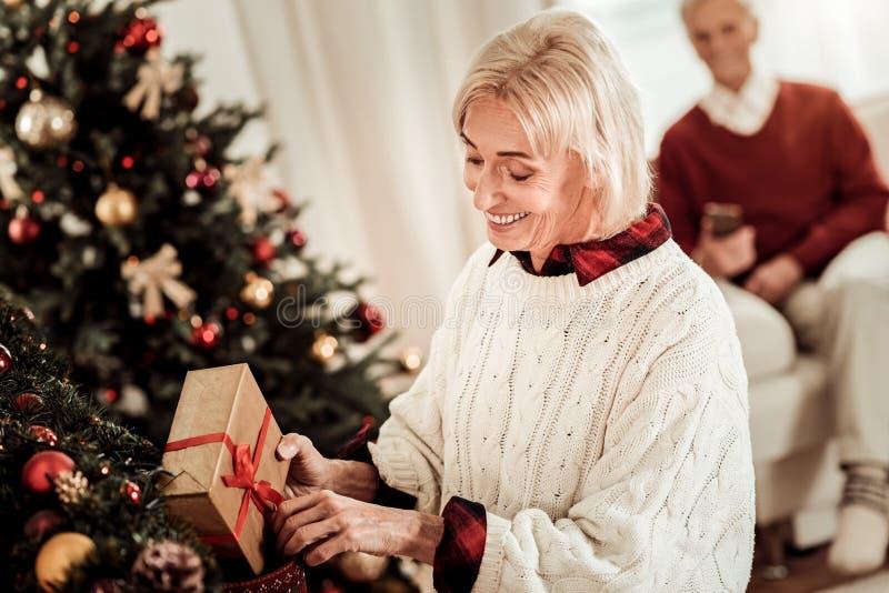 Mujer ocupada interesada que sonríe y que oculta un regalo fotografía de archivo