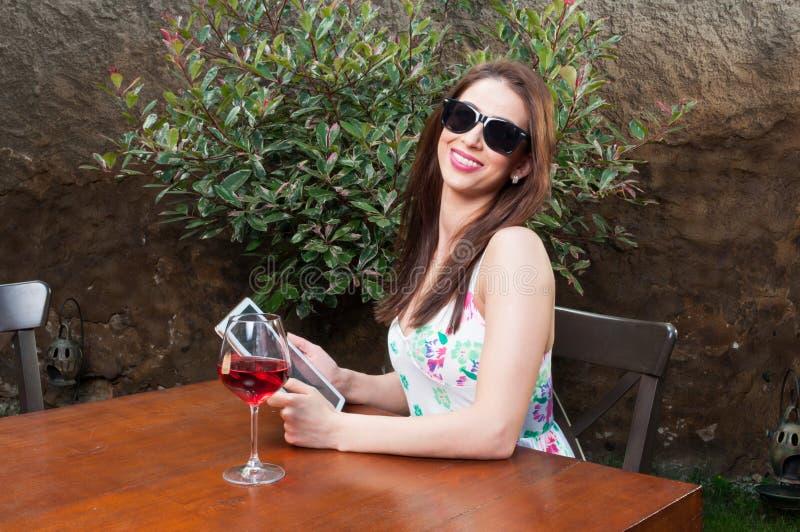 Mujer ocupada que come vino en la tableta de la tenencia de la terraza foto de archivo libre de regalías