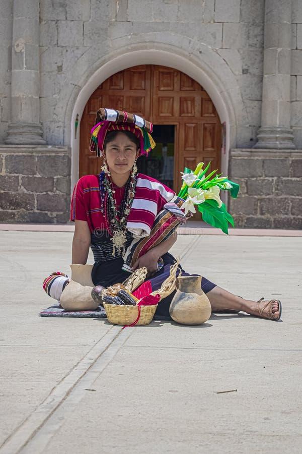 Mujer originaria de la identidad maya Mam con su típico vestido rojo con sus tradicionales jugos ultencilios, cesta, peraje, y fotos de archivo libres de regalías