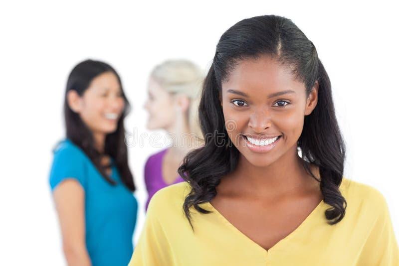 Mujer oscura sonriente que mira la cámara con dos mujeres detrás de ella imagenes de archivo