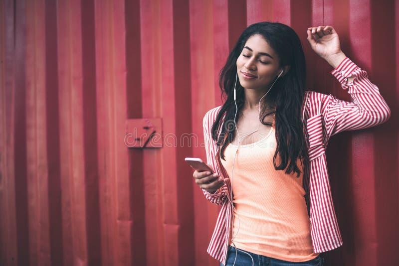 Mujer pacífica que disfruta de la música y que pone una mano imagen de archivo libre de regalías