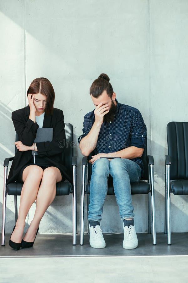 Mujer parada del hombre joven del fracaso de la entrevista de trabajo imagenes de archivo