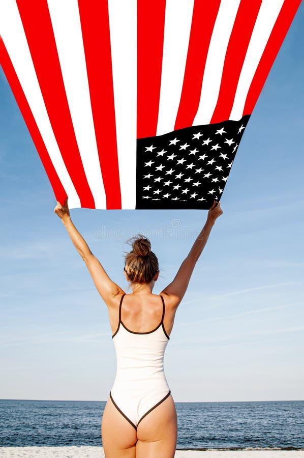 Mujer patriótica hermosa que sostiene una bandera americana en la playa Día de la Independencia de los E.E.U.U., el 4 de julio Co foto de archivo