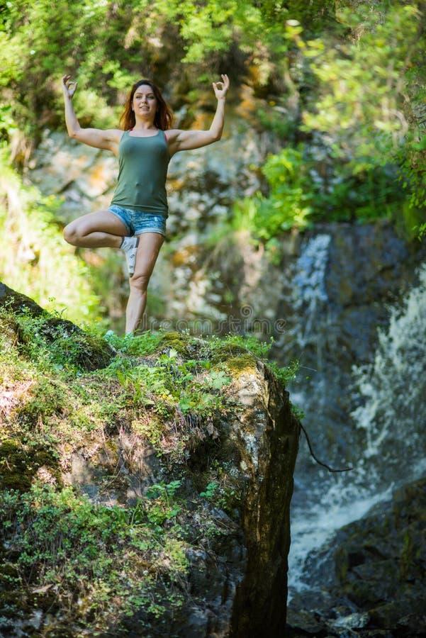 Mujer pelirroja en los pantalones cortos que hacen yoga en la cascada E imagen de archivo libre de regalías