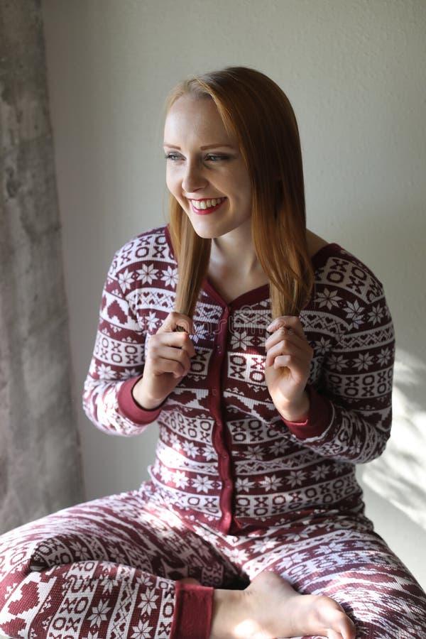 Mujer pelirroja en pijamas de la Navidad foto de archivo